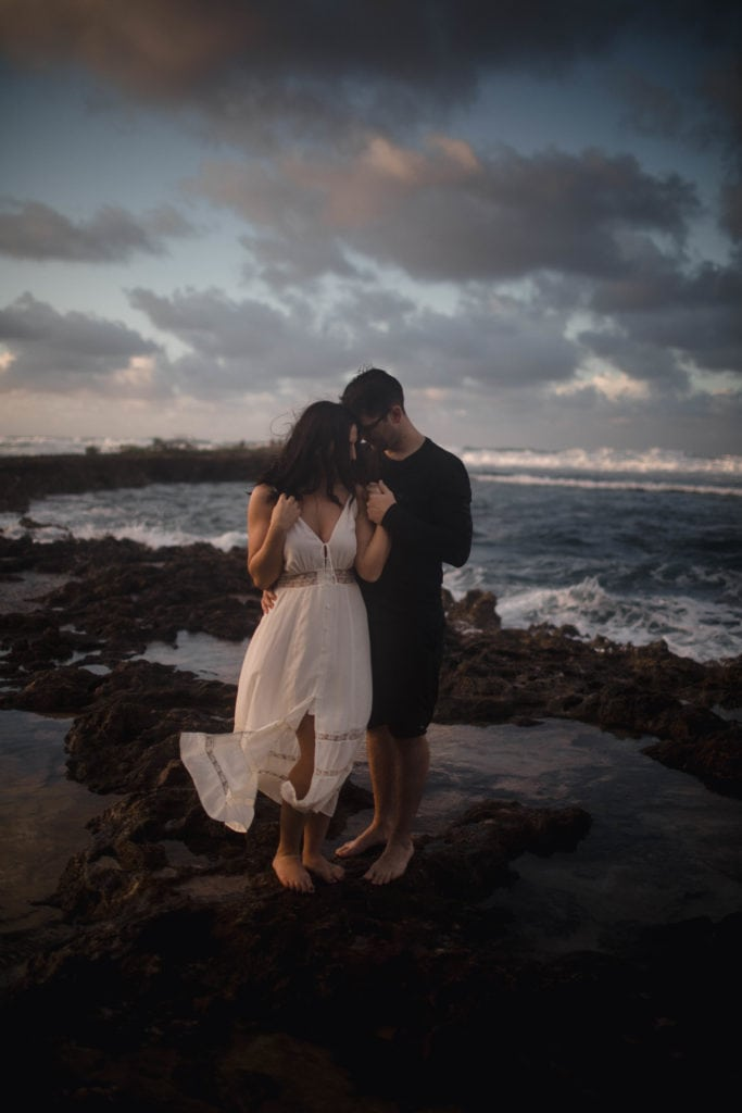 Couple on their honeymoon at the beach cuddling and taking honeymoon photos.